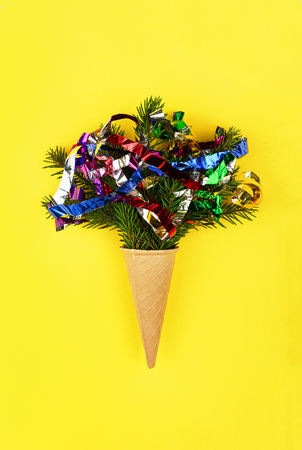 Christmas. New Year. Style minimalism. Christmas tree in ice cream cone on a yellow background. top veiw