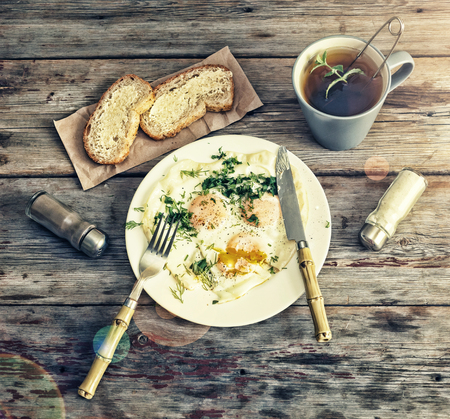Fried eggs with greens on a white plate.wooden background. top veiw Stock Photo