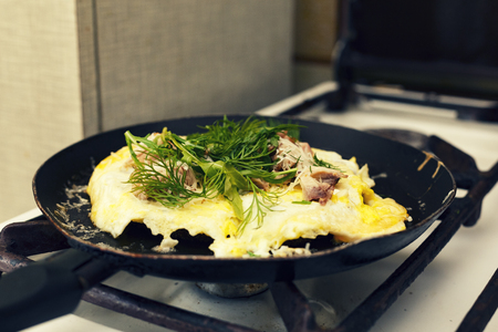Healthy breakfast. Omelette with bacon and arugula fried in a frying pan. close up Reklamní fotografie