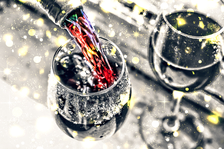 Pouring wine. Christmas wine. Christmas, falling snow, golden snowflakes. New Year close up