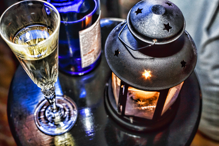 New Year Christmas. Champagne in glasses and in a bottle, a Christmas lantern with a burning candle on the festive table. close up Stock Photo