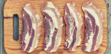 Bacon. Raw steaks on a cutting board. tio veiw