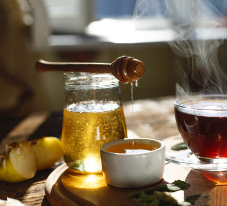 Pouring honey.Natural bee honey with morning tea.close up Stock Photo