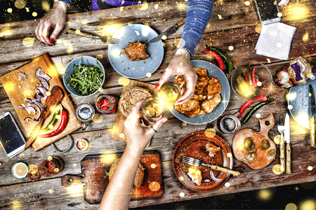 Meeting friends at the Christmas table. Traditional American sandwiches and bagels, beer and wine. Falling golden snowflakes. Stockfoto