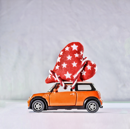 Toy car delivering hearts for Valentine's Day against the backdrop of a colorful bokeh. close up Stock Photo