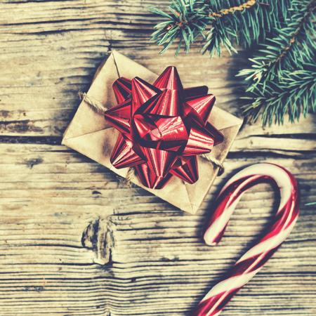 Nový rok dárek v domácí krabici s červeným lukem poblíž chlupaté smrky větve a Christmas Candy canes.top zobrazení Reklamní fotografie