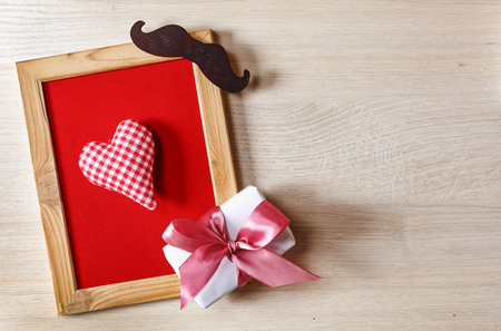 Father's Day Background Heart in a frame on a red background, with a gift box and black mustache. Happy father's day Free space for text. Banque d'images