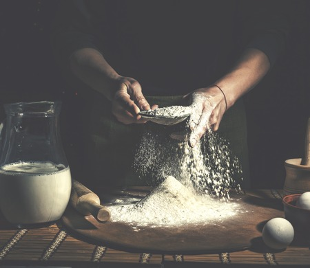 Preparation of Easter bread.Man preparing bread dough on wooden table in a bakery close up. Archivio Fotografico