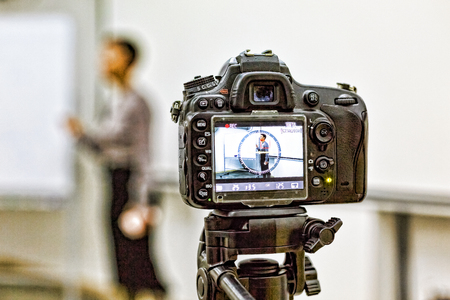 A digital camera on a tripod removes the lecturer, speaking in front of the audience.institute, university, college