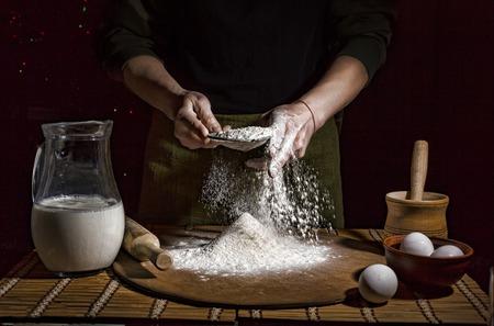 Homem que prepara a massa de pão na tabela de madeira em um fim da padaria acima. Preparação de pão de Páscoa.