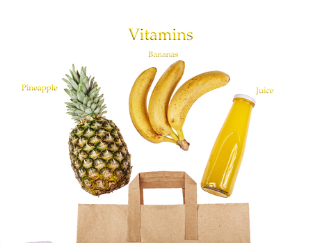 A paper bag with exotic fruits and fruit juice. Pineapple, bananas and a bottle of juice on a white background. The concept: fruit vitamin juices