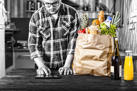Full paper bag of vegetables and fruits, various food and drinks on a wooden table close up. In the background, a person makes purchases via the Internet using a tablet