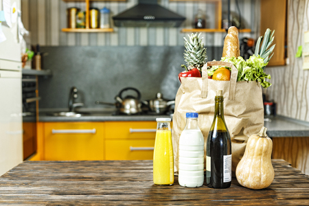 Paper bag with various food is on the table in the kitchen.