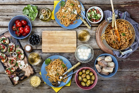 Top view of various Italian dishes with red and white wine on the wooden table. free space for text. copy space.