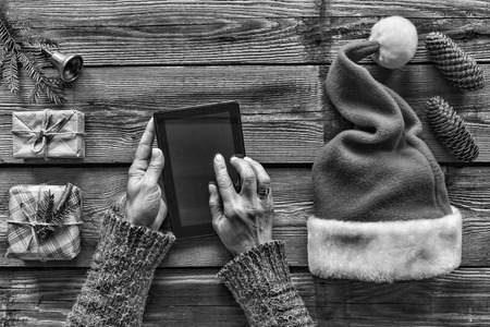 black and white. Conception: Preparation of Christmas gifts. A man holds a tablet PC in his hands and packs Christmas presents. top view