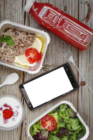 Healthy food. Concept: Proper nutrition, catering, business lunch. Smartphone with white screen and wholesome food in disposable containers on a wooden background. top view