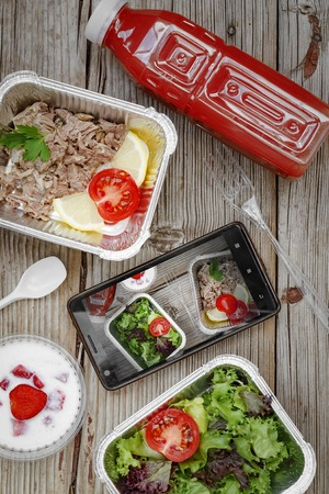 Healthy food. Concept: Proper nutrition, catering, business lunch. Smartphone and wholesome food in disposable containers on a wooden background. top view