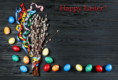 Easter, Easter eggs, Easter eggs and Bouquet of flowering branches of pussy-willows with colorful ribbons ON A BLACK WOODEN BACKGROUND. Stock fotó