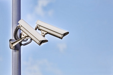 two security surveillance Laterally camera on a post in bue sky, copy space