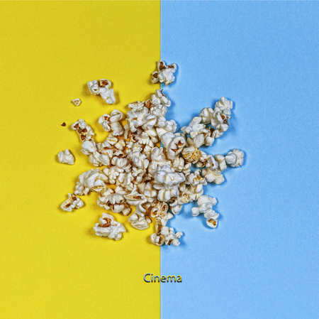 Minimal style. Popcorn on a yellow and blue background. Concept: Cinema