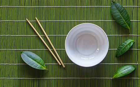 Empty poke bowl, japanese table setting with tropical leaves. Bamboo mat, chopsticks