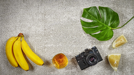 Vintage camera on a stone background with tropical leaves, a glass of whiskey and tropical fruits. Concept: Travel Vacation