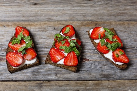 Healthy food. sandwiches with cream and strawberries on a wooden background.