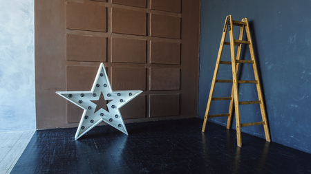 Interior of a modern studio. A free wall, a star-shaped lamp and a ladder by the wall. Creative location Reklamní fotografie