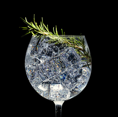 Cocktail alcolico con ghiaccio, soda e rosmarino su sfondo nero