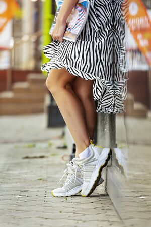 Women's Legs of in ultra fashionable clothe, white sneakers and a striped skirt modern city. Young woman walking down the street on a summer day and posing by the wall. New collection of fashionable modern shoes.
