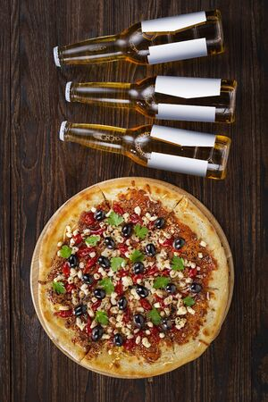 Bottle beer and pizza on a wooden background. Vertical composition. Overhead view Stock Photo