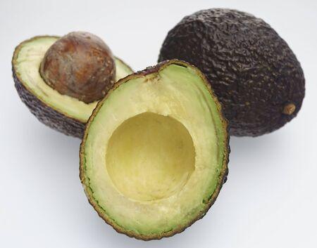 Ripe Avocado Haas. Avocado fruit whole and cut in half on a white background Zdjęcie Seryjne