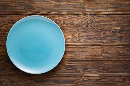 Piatto blu vuoto su un tavolo di legno.