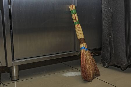 Broom sweeps garbage on the floor in the restaurants kitchen