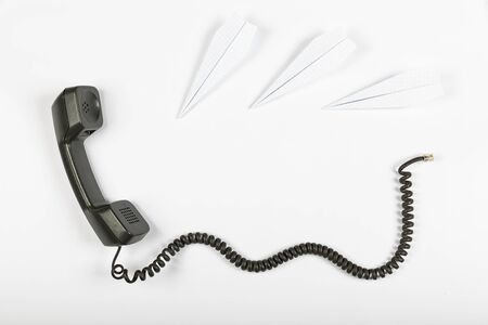 Call center concept, public relations, gossip, rumors. Telephone receiver with wire on a white background and paper airplanes. Stok Fotoğraf