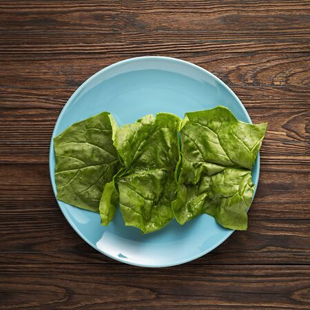 crispy spinach leaves on a blue dish on a wooden background, top view