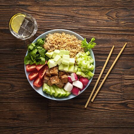vegetarian poke bowl with vegetables and quinoa on a wooden table. Healthy food, vegetarian food. Buddha plate Archivio Fotografico - 131496259