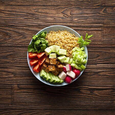 Vegetarische Poke Bowl mit Gemüse und Quinoa auf einem Holztisch. Gesundes Essen, vegetarisches Essen. Buddha-Teller