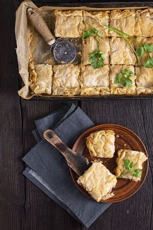 Meat pie with cilantro on a wooden table. Rustic style, top view.