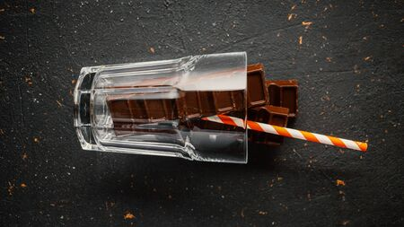 Chocolate party concept. Cold chocolate in a glass of cola lies on its side. Party concept. Reklamní fotografie