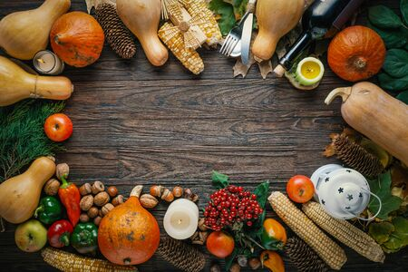 Thanksgiving frame from autumn vegetables and fruits on wooden background with copy space in the center of the composition