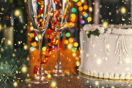 Christmas and New Year celebration concept. Champagne, glasses and holiday cake near the Christmas tree with decorations. Zdjęcie Seryjne
