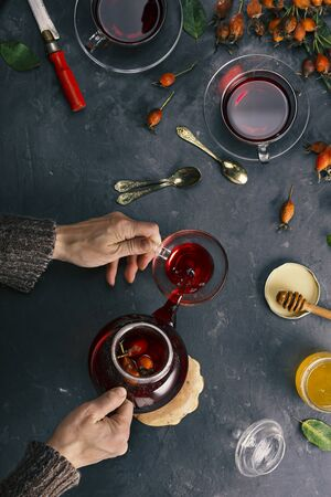 Woman is preparing tea from rose hips.