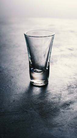 Empty vodka glass on dark table