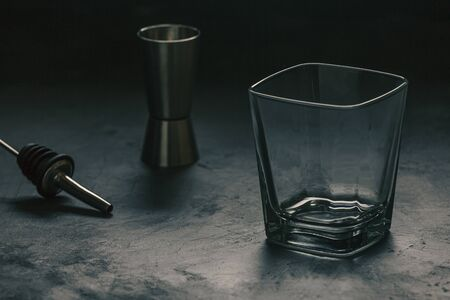 Faceted glass for an alcoholic drink and bartender tools on a dark background.
