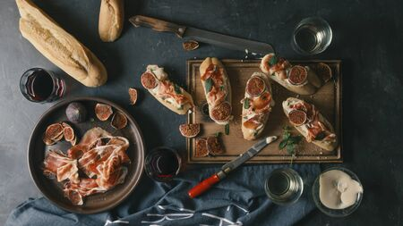 Spanish snacks and wine on a dark concrete background. tapas, pinchos, bruschetta of Delicious ham, jamon, baguette, figs, cheese and herbs on the dining table. Stock Photo