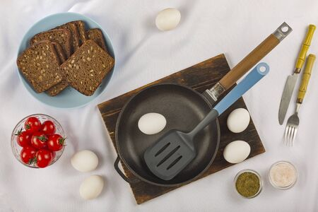 Cooking breakfast. Eggs, cherry tomatoes and dark bread cereal. Eco food.