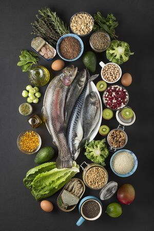 Concept Source OMEGA-3. Foods containing omega -3: sea fish, green vegetables, seeds, oil fish oil Stock Photo