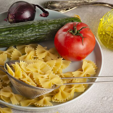 Raw farfalle pasta, vegetables and spices. Italian cooking
