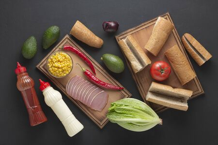 Ingredients for a sandwich on a wooden board. Homemade sandwiches with ham and vegetables.
